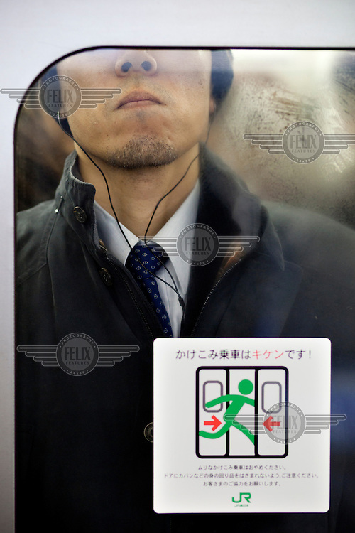 A commuter, wearing a set of headphones, crammed into one of the train carriages at Shibuya station during morning rush hour.
