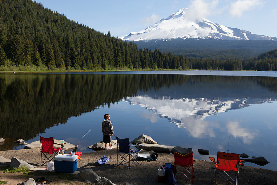 Boy at his family's campsite at Mount Hood reflected in Trillium Lake, Oregon, OR, USA