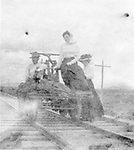 Two women and a man posing on a hand car.  Location very unknown.  Track looks to be two-rail narrow gauge.<br /> D&amp;RG ?    ca 1910