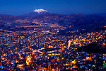Snowcapped Mt Illimani overlooks an illuminated La Paz city at dusk.  The city sits in a canyon surrounded by the high mountains of the Altiplano.