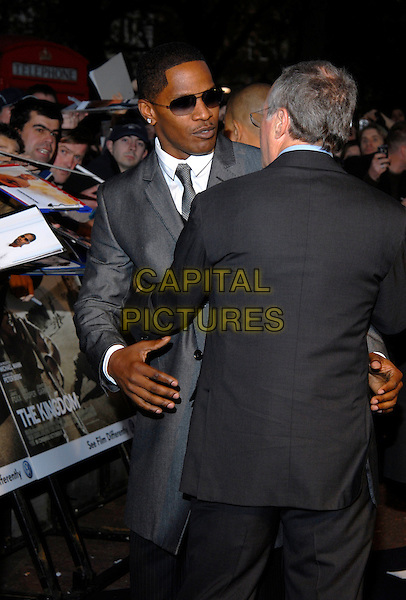 "JAMIE FOXX & MICHAEL MANN.""The Kingdom"" - UK film premiere, Odeon West End, London, England. .October 4th, 2007.half length black suit grey gray jacket back behind rear hug embrace sunglasses shades .CAP/IA.©Ian Allis/Capital Pictures"