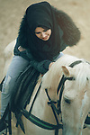 A happy woman petting a white horse. Photo by Sanad Ltefa