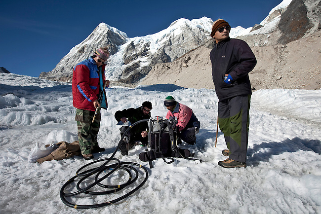 Dr Shresth Tayal(right), Glaciologist at The Energy and Resources Institute (TERI) supervises his team (from left)  Phurbu Tsering Butia, Mohammad Ashraf Genai and Sanjay Balmiki set  equipment on the fast reducing Rathong Glacier  below the 6678 meter Rathong Peak (at rear) in the North East Indian state of Sikkim close to the Nepalese border. Considered to be a themometre of the environment, it has been chosen by TERI to be a test case of environmental damage being done in India and China. Dr. Tayal is conducting three dimensional tests that include measuring the depth of the ice to form concrete conclusions on the fate of the glacier.The Indian Government is denying the glaciers' demise despite data suggesting it has been reduced by more than over 80% in the last 42 years.