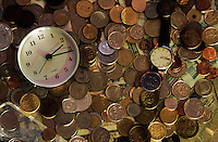 Clock and a wristwatch on a bed of international coins.
