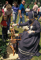 AJ1819, spinning wheel, artisan, antique, demonstration, wool. Georgia. A woman spins yarn from wool on a spinning wheel as people watch at the Dogwood Festival in Piedmont Park in Atlanta, Georgia.