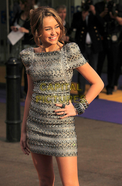 "MILEY CYRUS .UK Premiere of ""Hannah Montana: The Movie"" at the Odeon Leicester Square, London, England, UK, April 23rd 2009..half length grey gray silver beaded embellished dress hand on hip hair up bracelets bangles shoulder pads shoulders .CAP/CAS.©Bob Cass/Capital Pictures"