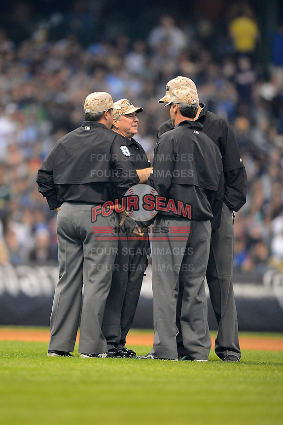 Umpires Dana DeMuth, Doug Eddings, Angel Hernandez, and Jordan Baker discuss a ball hit by Joe Mauer (not pictured) that went to video review and called a home run during a game between the Milwaukee Brewers and Minnesota Twins at Miller Park on May 27, 2013 in Milwaukee, Wisconsin.  Minnesota defeated Milwaukee 6-3.  (Mike Janes/Four Seam Images)
