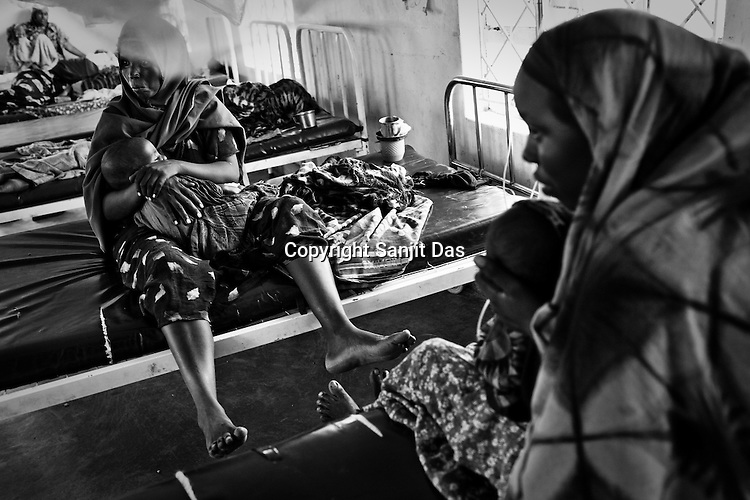 Somalian refugees seen with their malnourished children inside the stabilization ward of the GIZ Main Hospital in the Dadaab refugee camp in northeastern Kenya. Hundreds of thousands of refugees are fleeing lands in Somalia due to severe drought and arriving in what has become the world's largest refugee camp. Photo: Sanjit Das/Panos`