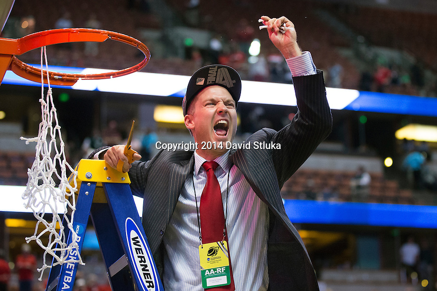 Wisconsin Badgers basketball director of communications Patrick Herb cuts down a piece of the net after the Western Regional Final NCAA college basketball tournament game against the Arizona Wildcats Saturday, March 29, 2014 in Anaheim, California. The Badgers won 64-63 (OT). (Photo by David Stluka)