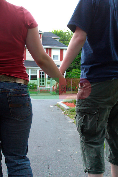teenage boy and girl walking holding hands in suburban neighborhood, young love