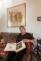 Switzerland. Canton Ticino. Sala. Elsy (Elsa) Hofer Ferrari Ramuz is 86 years old. She seats at home on a sofa in her living room. She holds in her hands a family photo album with black and white (B&W, B/W) pictures. On the wall, a painting by the artist Irène Zurkinden on the Basel Carnival. Elsy Hofer Ferrari Ramuz is the niece of Charles-Ferdinand Ramuz (September 24, 1878 – May 23, 1947) who was a French-speaking Swiss writer. 14.11.2017 © 2017 Didier Ruef