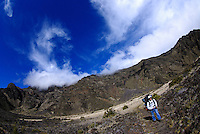Hiker crossing Haleakala crater under a dynamic sky, Maui