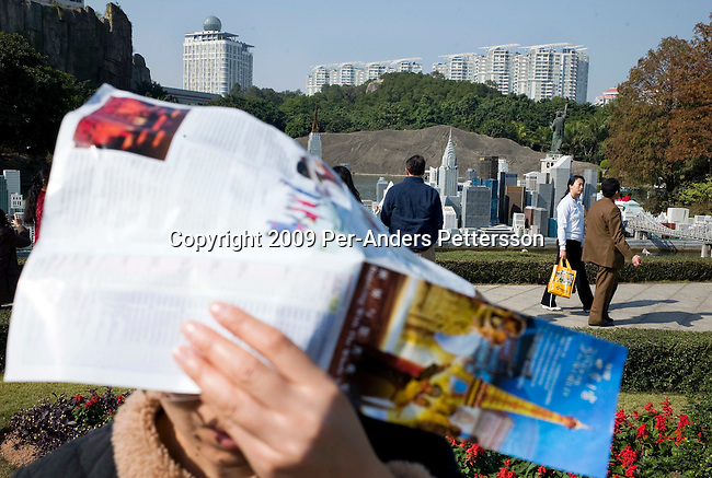 SHENZHEN, CHINA JANUARY 1: A Chinese tourist covers his head with a map at the Manhattan miniature section at Windows Of the World Theme park on January 1, 2009 in central Shenzhen, China. The park, one of China's most popular, gives Chinese and tourists a view of famous landmarks around the world as miniatures, without traveling around the world. There are copies of the Eiffel Tower, Manhattan, and Pyramids, London, Venice, Rome etc. Chinese people love theme parks and new ones are opening constantly. It's estimated that there's about 2400 theme parks in the country. Many Chinese cannot afford to travel to Europe or America and the park gives them a chance to see famous landmarks. (Photo by Per-Anders Pettersson)..