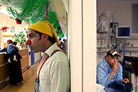 """Mustafah Mshasha, a Palestinian boy from the Old City of Jerusalem receives chemotherapy at the Oncology Day Care unit at Hadassah Ein Karem hospital, as clown Dudi (Dudy Barashi an Israeli  medical clown who works in Hadassah member of a group call """"Dream Doctor"""") visits other patients. ..Mustafa suffers from Leukemia and has been treated in the Children Oncology Unit. Photo by Quique Kierszenbaum"""