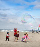 USA, Washington State, Long Beach Peninsula, Thorson kids chase and play with bubbles on the beach at the International Kite Festival