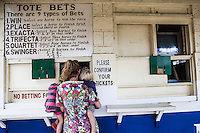 A woman palced a bet at the races at Ngong Racecourse in Nairobi, Kenya. March 17, 2013 Photo: Brendan Bannon