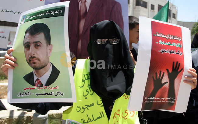 Palestinian Hamas supporters hold up pictures of relatives who were arrested and imprisoned for political reasons by Palestinian Authority security forces, during a protest in the West Bank city of Hebron, on June 09,2011. Photo by Najeh Hashlamoun