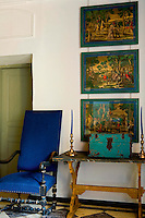 A Louis XIII chair is covered in modern blue linen beside  a 17th century Florentine table in the hall above which is a series of antique prints illustrating the life of Don Quixote