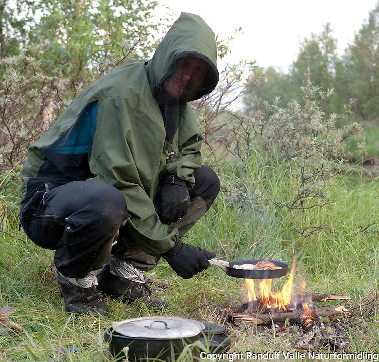 Mann med myggjakke, hansker og buksa tapet fast til skoene lager middag en kveld med mye insekter. ---- Man with bug shirt cooking.