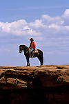 AZ, Monument Valley, Bruce, Native American Navajo Indian on horseback, stone bluff .Photo Copyright: Lee Foster, lee@fostertravel.com, www.fostertravel.com, (510) 549-2202.Image: azmonu203