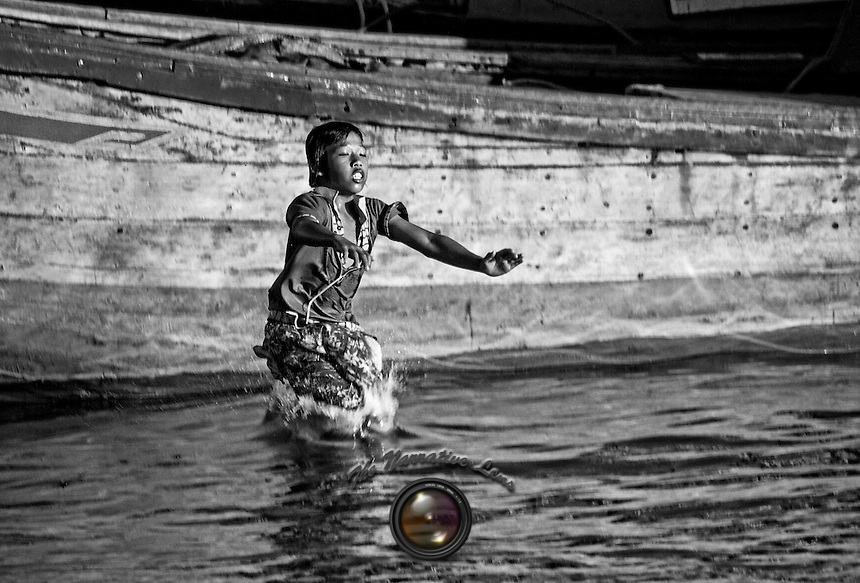 I saw this young fellow just before he leaped off of his father's boat into the murky water in the harbor in Nha Trang.