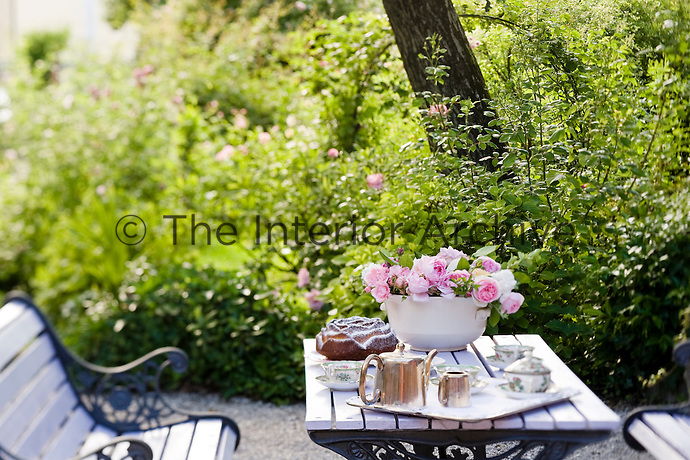 A simple tea is served on a wooden table in a quiet part of the garden
