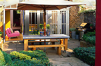A zinc topped oak table with an umbrella is the perfect place for dining in the courtyard