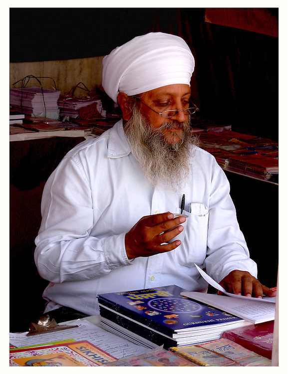 A book vendor and scholar of Sikhism sits at a table drinking coffee in a white turban while reading from one of the many books he offers to devotees from his store under the marble arches of Gurudwara Bangla Sahib (a prominent Sikh house of worship) in Delhi, India.