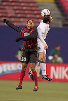 The MetroStars' Amado Guevara  goes up for a header with New England Revolution's Joe-Max Moore. The New England Revolution played the NY/NJ MetroStars to a 1 to 1 tie at Giant's Stadium, East Rutherford, NJ, on April 25, 2004.