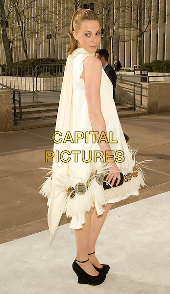 """ELETTRA WIEDEMANN (daughter of Isabella Rossellini).Opening Night of """"La Fille du Regiment"""" at The Metropolitan Opera, Lincoln Center, New York, NY, USA..April 21st, 2008.full length white sleeveless feather dress  black shoes looking over shoulder scarf wedges clutch bag gold circles cream.CAP/LNC/TOM.©TOM/LNC/Capital Pictures."""
