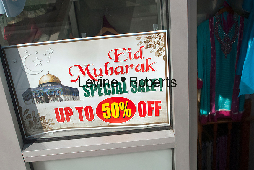 A clothing store announces a big sale for the Muslim holiday of Eid ul-Fitr in the Jackson Heights neighborhood in Queens in New York on Sunday, October 14, 2012. The Jackson Heights neighborhood is home to a mosaic of ethnic groups beside Indians which include Pakistanis, Tibetans, Southeast Asian and long-time Jewish and Italian residents.  (© Richard B. Levine)