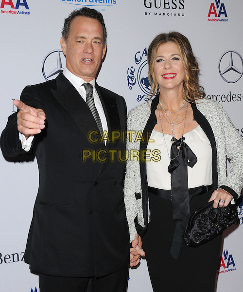 TOM HANKS & RITA WILSON .at The 32nd Annual Carousel of Hope Ball held at The Beverly Hilton hotel in Beverly Hills, California, USA, .October 23rd 2010..half length black suit tie married husband wife white top jacket holding hands bow ribbon clutch bag silver finger pointing  skirt dress                              .CAP/RKE/DVS.©DVS/RockinExposures/Capital Pictures.
