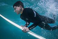 Manuel dives under a wave in Doniños beach. Galicia, Spain.