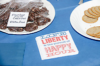 "A napkin reading ""Life Liberty and the pursuit of Happy Hour"" lays on the dessert table at the Milford Democrats' Potluck Supper at the Unitarian Universalist Congregation Church in Milford, New Hampshire, USA, on Sat., Apr. 6, 2019. Democratic presidential candidate and Congressional Representative Eric Swalwell (D-CA 15th) spoke at the event. Swalwell is running primarily on gun control issues."
