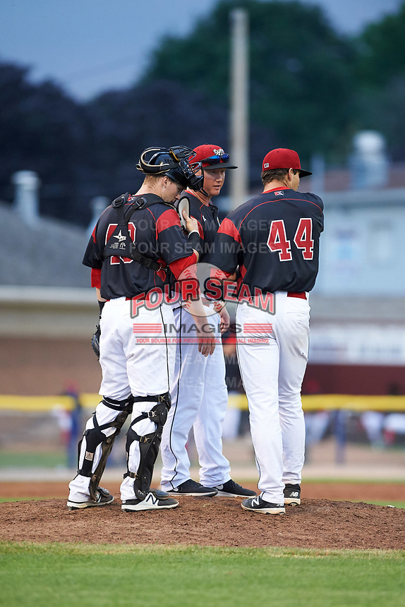 Batavia Muckdogs pitching coach Jason Erickson (16) talks with pitcher Sam Perez (44) and catcher Alex Jones (43) during a game against the Tri-City ValleyCats on July 14, 2017 at Dwyer Stadium in Batavia, New York.  Batavia defeated Tri-City 8-4.  (Mike Janes/Four Seam Images)