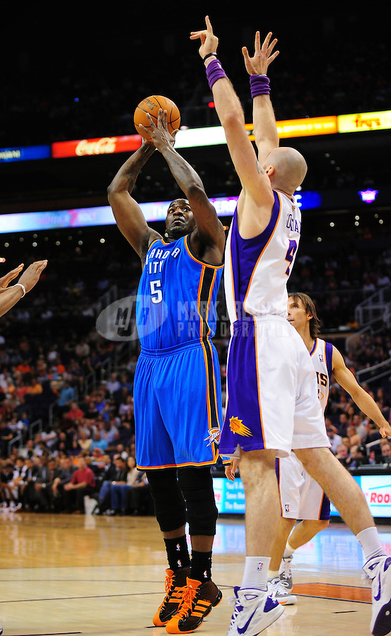 Mar. 30, 2011; Phoenix, AZ, USA; Oklahoma City Thunder center (5) Kendrick Perkins takes a shot under pressure from Phoenix Suns forward Marcin Gortat at the US Airways Center. Mandatory Credit: Mark J. Rebilas-
