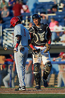Batavia Muckdogs catcher Brad Haynal (23) talks with batter Edwin Lora (1) during a game against the Auburn Doubledays July 10, 2015 at Dwyer Stadium in Batavia, New York.  Auburn defeated Batavia 13-1.  (Mike Janes/Four Seam Images)