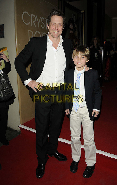 Hugh Grant & Damien Hurley ( son of Elizabeth Hurley ).The 'The Pirates! In An Adventure With Scientists' UK film premiere, The Crystal Room,  May Fair Hotel, Stratton St., London, England..March 21st, 2012.full length black suit jacket white shirt beige trousers tie kid child hand on hip .CAP/CAN.©Can Nguyen/Capital Pictures.