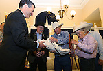 Gov. Brian Sandoval recieves a petition from a group of ranchers, including from left, Assemblyman Ira Hansen and Pete and Lynn Tomera at the Capitol in Carson City, Nev., on Friday, May 30, 2014. About 40 people rode horses into downtown Carson City today to deliver a petition to the governor calling attention to the ongoing fight between ranchers and the BLM over grazing on public lands. <br /> Photo by Cathleen Allison