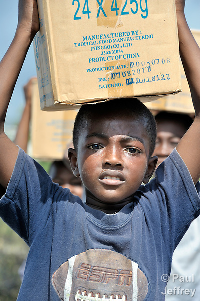 A boy living in a camp for homeless families helps unload food aid in Jacmel, a town on Haiti's southern coast that was ravaged by the January 12 earthquake.