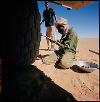 Sahara desert, Libya-Chad, November/December 2004..Every week, a convoy of 40 privately owned Libyan trucks loaded by the WFP with about 1000 metric tons of western food aid cross 2500 km of deep desert across Libya and Chad to reach more than 200 000 refugees from Darfur in camps near the Sudanese border. Mashalla, the Libyan convoy leader discusses with Abdallah, his Sudanese mechanic changing a wheel; punctures are extremely frequent, the trucks are loaded to the limit and some rocks are razor sharp...