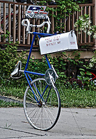 A creative bike shop owner created an unique and eyecatching rural mailbox created by using an old, blue racing bicycle standng on one wheel as a post for the box.