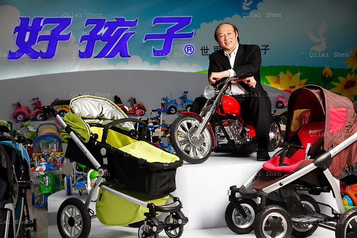 Song Zhenghuan, chief executive officer and chairman of Goodbaby Child Products Company, poses for photographs while straddling a toy motorcycle that Goodbaby makes at the company's showroom in Kunshan, Jiangsu Province, China, on Monday, May 04, 2009.Once a middle school teacher, Mr. Song is now a self-made billionaire industrialist, his company is China's largest manufacturer and supplier of infants' and children's products.