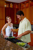 Couple enjoying making food at stove