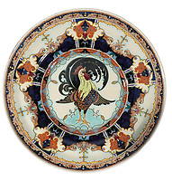 BNPS.co.uk (01202 558833)<br /> Pic: Duke's/BNPS<br /> <br /> A plate decorated with a cockerel.<br /> <br /> A collection of pottery that belonged to late Blue Peter presenter John Noakes is being sold by his widow for around £10,000.<br /> <br /> The 29 pieces of Rozenburg porcelain were collected by the 1970s TV star right up until his death, three years ago in 2017.<br /> <br /> Since then they have been in the ownership of his wife Vicky who has now decided the time is right to put them on the market.