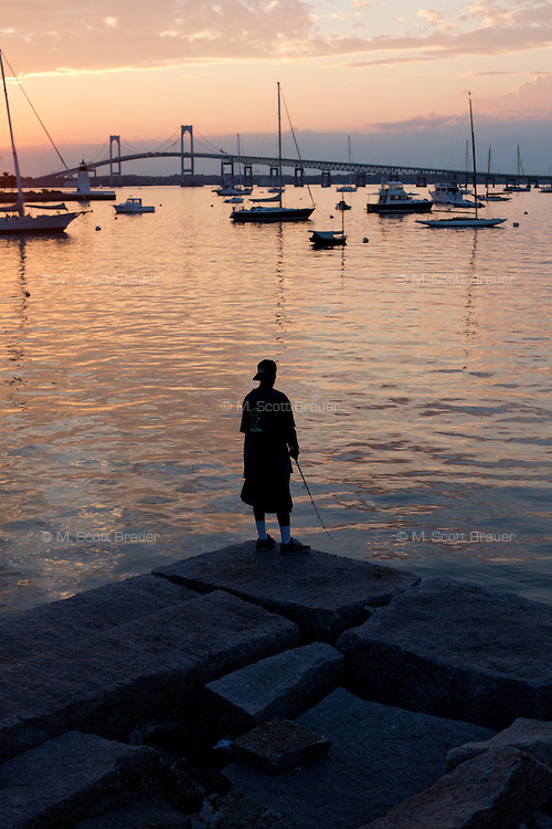 A man fishes from the bank in Newport, Rhode Island, USA.  The Newport Bridge is visible in the background.