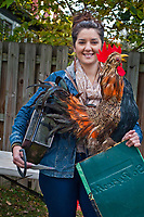 Jenna Growzinger holds a giant rooster and other items she bought at an estate auction.<br /> <br /> The contents of a home on East Broadway went before the auction block Saturday. <br /> <br /> Eager bargain hunters took their time looking over prospective purchases hoping others didn't know of its true value or weren't interested in their item of choice.<br /> <br /> Many boxed items were sold with the buyer only interested in one item in the box of interest. Many buyers bought large lots of glass and pottery for a single knickknack in the collection.