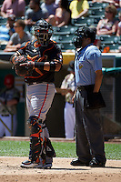 Guillermo Quiroz (41) of the Fresno Grizzlies behind the plate with home plate umpire Alex Ortiz during the game against the Salt Lake Bees at Smith's Ballpark on May 26, 2014 in Salt Lake City, Utah.  (Stephen Smith/Four Seam Images)