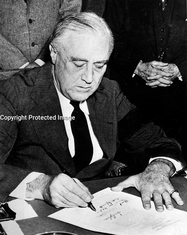 President Franklin D. Rossevelt signing the declaration of war against Japan, December 8, 1941.  (National Park Service)<br /> NARA FILE #:  079-AR-82<br /> WAR &amp; CONFLICT BOOK #:  743