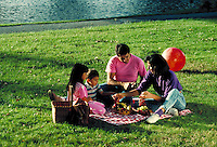 Young hispanic parents picnic on lawn of city park with children, girl aged 7 and boy aged five. young latino family.